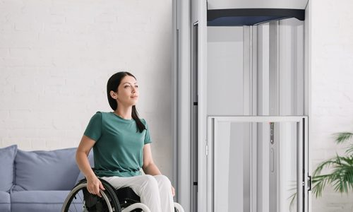 smiling disabled woman looking away while sitting in wheelchair at home